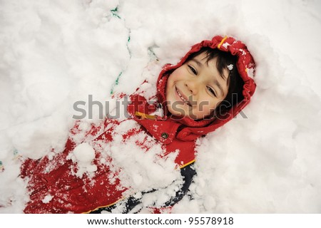 Little boy covered with snow - stock photo