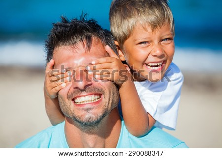 Little boy covers his dads eyes while playing at the beach - stock photo