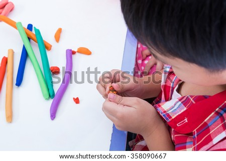 Little boy creating toys from play dough. Child moulding modeling clay. Strengthen the imagination of child - stock photo