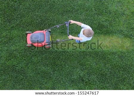 Little boy cuts a lawn using lawn-mower - stock photo