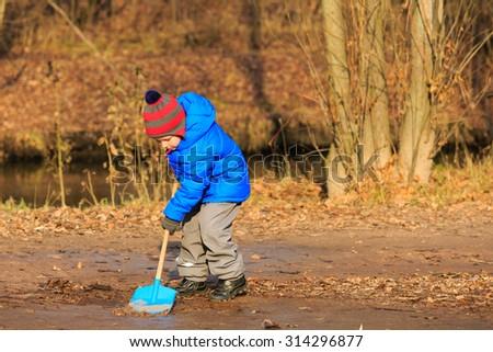 little boy digging in autumn park, autumn kids activities - stock photo