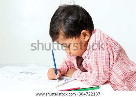 little boy drawing cartoon with crayons. - stock photo