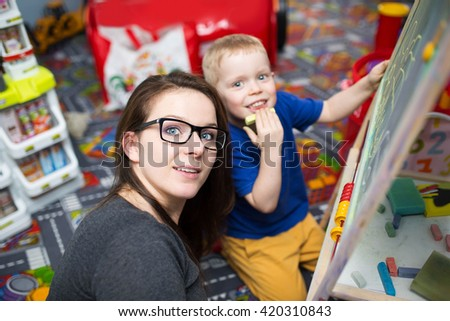 Little boy drawing on the blackboard and his big sister looking after him. - stock photo
