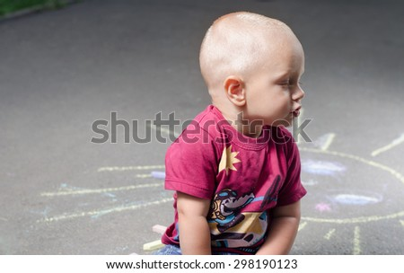 little boy draws with chalk on the pavement sun  - stock photo