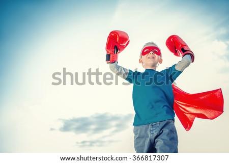 Little boy dressed as superhero outdoors - stock photo