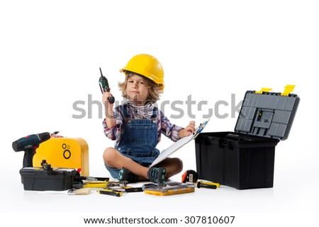 Little boy dressed as utility worker with protective helmet trying to figure out how the drill works - stock photo