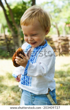 Little boy dressed in ukrainian embroidered costume outddor - stock photo