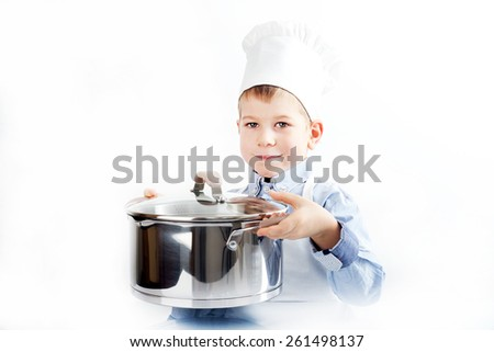 Little boy dressed like a chef making diner - stock photo