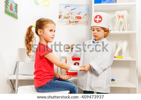 Little boy dressed like a pediatrician doctor bandaging girl's arm with a roller-bandage at the first aid room - stock photo