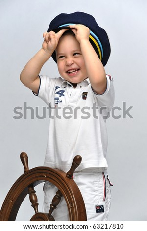 Little boy dressed up as a sailor standing next to the steering wheel - stock photo