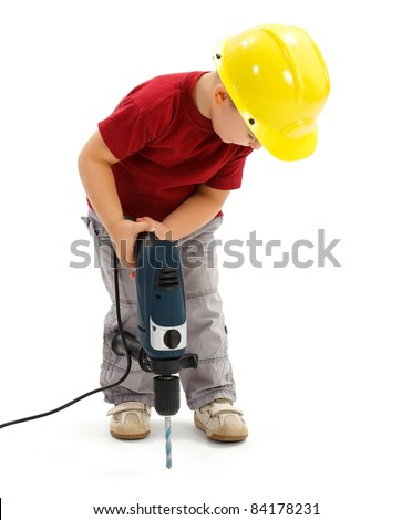 Little boy drilling in ground with real drill, wearing yellow protective helmet, imitating handyman - stock photo