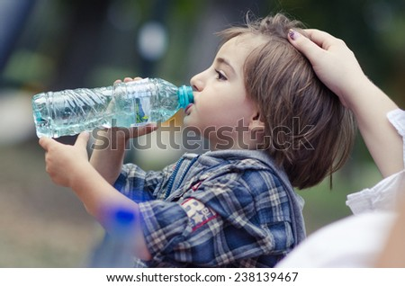 Little boy drink water, outdoor - stock photo