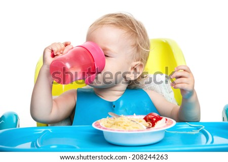 Little boy drinking water while sitting at table with plate of spaghetti  - stock photo