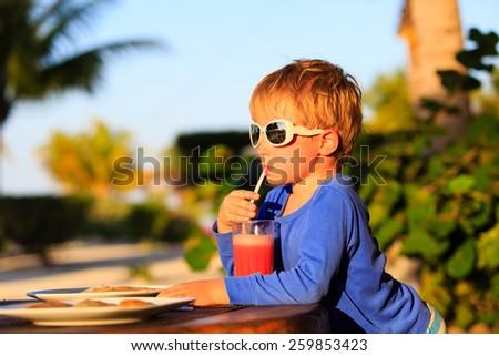 little boy drinking watermelon juice on tropical beach - stock photo