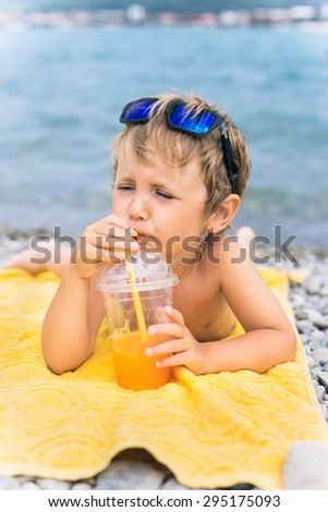 Little boy drinks juice on beach against the sea - stock photo