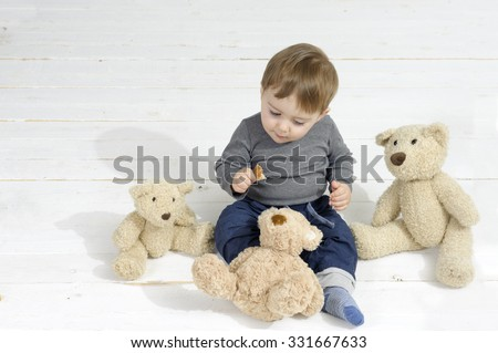 Little boy eating a piece of bread, surrounded by three teddy bears - stock photo