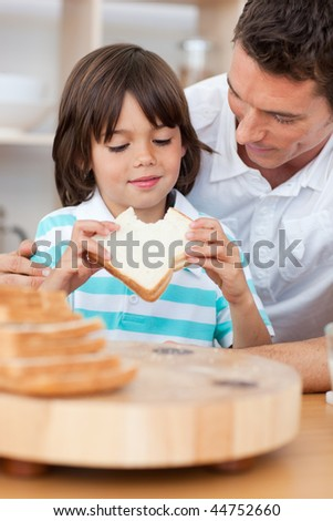 Little boy eating a sandwich with his father in the kitchen - stock photo