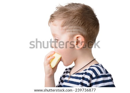 Little boy eating an apple on a white background. profile - stock photo