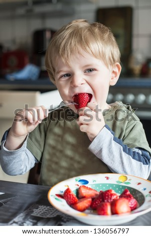 Little boy eating fresh strawberries in the kitchen - stock photo