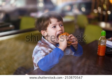 Little boy eating hamburger in fast food restaurant behind glass - stock photo