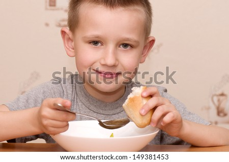 Little boy eating soup  - stock photo