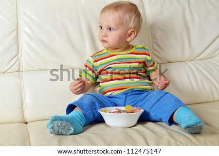 Little boy eating sweets. full bowl of candy - stock photo