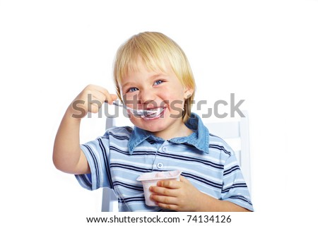 Little boy eating yogurt isolated on white background - stock photo