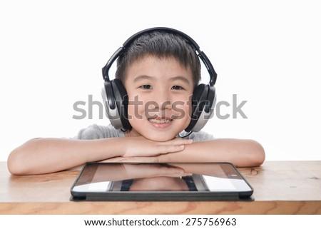 little boy enjoying music using headphones, with smart phone on long wooden chair - stock photo