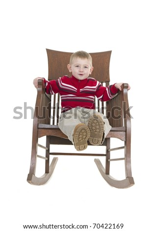 little boy enjoys playing on an antique wooden rocking chair - stock photo