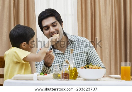 Little boy feeding piece of pizza to father at restaurant - stock photo
