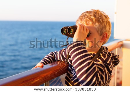 little boy feeling adventurous while cruising and using the binoculars - stock photo