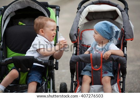 little boy gives water bottle to girlfriend - stock photo