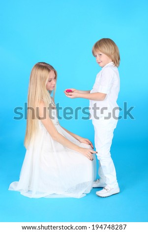 little boy giving a flower to his sister - stock photo