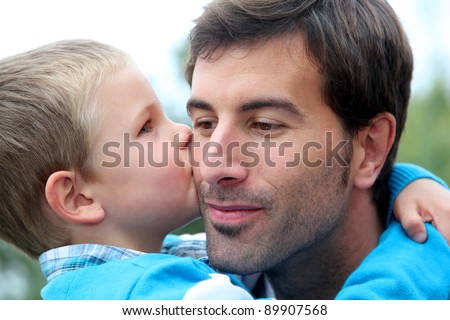 Little boy giving daddy a kiss - stock photo