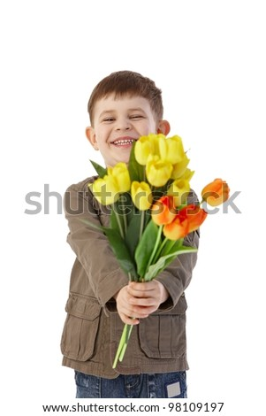 Little boy giving flowers to someone, smiling happily. - stock photo