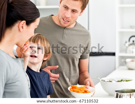 Little boy giving his mother a carrot while preparing lunch in the kitchen - stock photo