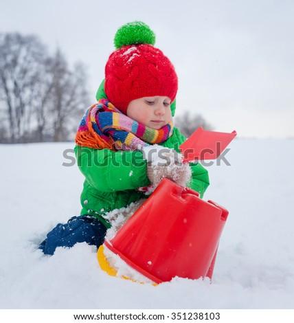 Little boy having fun in the snow - stock photo