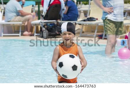 little boy having fun with a ball in a swimming pool - stock photo