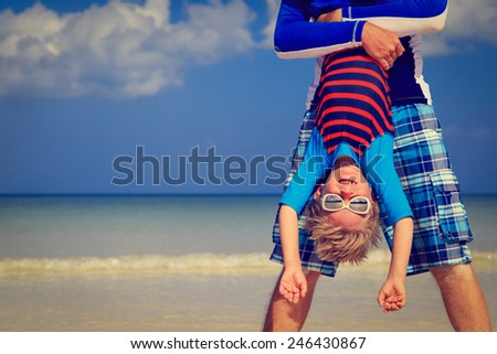 little boy having fun with dad on summer beach vacation - stock photo