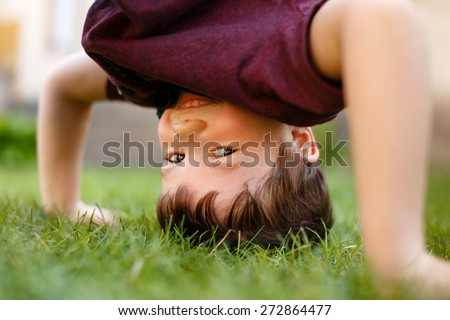 Little boy headstand in grass and laughing, outdoor portrait - stock photo