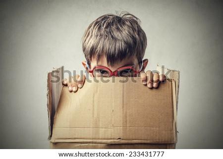Little boy hiding in a box  - stock photo