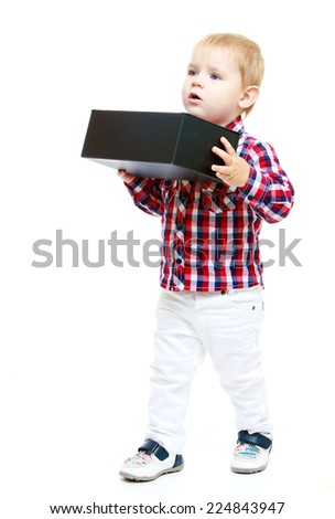 Little boy holding a big black box.Early years learning a happy childhood concept.Isolated on white background. - stock photo