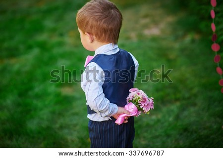Little boy holding a bouquet of flowers behind his back. - stock photo