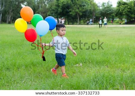 Little boy holding a bunch of balloon - stock photo