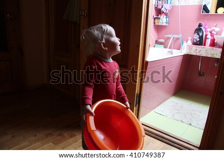 Little boy holding a plastic basin at home - stock photo