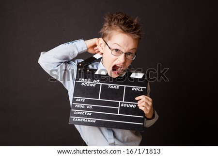 Little boy holding clapper board in hands. Cinema concept. - stock photo