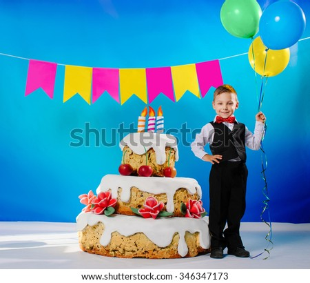 little boy holding colorful balloons near big birthday cake with candles and smiling on a blue background - stock photo
