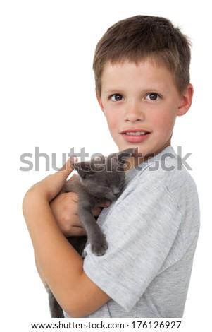 Little boy holding grey kitten smiling at camera on white background - stock photo