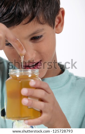 Little boy holding jar of honey - stock photo