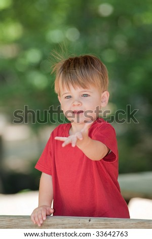 little boy holding out hand in an outdoor park - stock photo